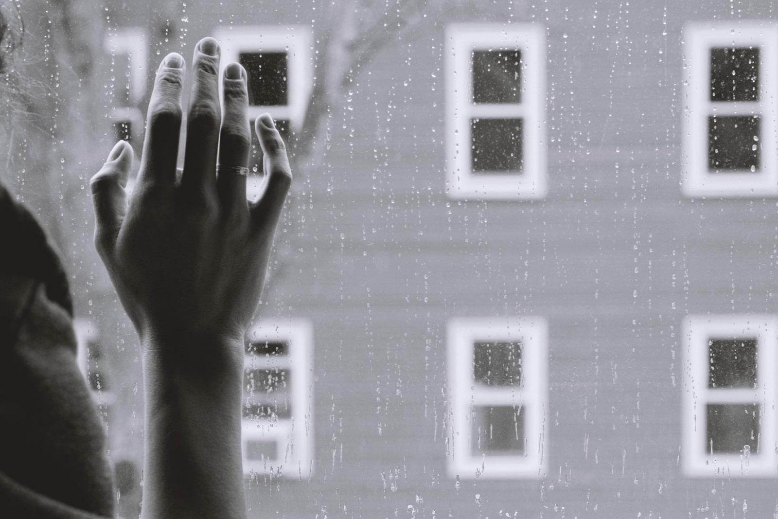 ガラス越しの雨と窓に触れる女性の手